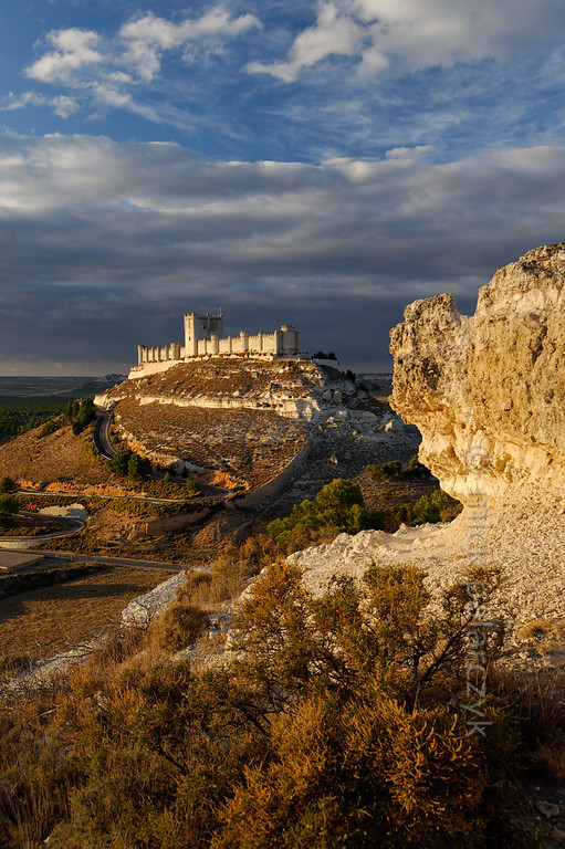 [SPAIN.CLEON 28635] 'Peñafiel Castle.'  Peñafiel Castle (Valladolid province) sits atop a narrow ridge of limestone like an imitation of Noah's Ark stranded on the summit of Mount Ararat. The original castle on this site was part of the 9th-10th century Moorish defense line against the Christians along the Duero river. In 1013 it was taken by the Castilians and rebuilt in the 13th and 14th centuries. The central keep was finished in the 15th century. As Peñafiel is located in one of Spain's most famous vine growing regions, the castle nowadays is home to a Wine Museum. Photo Mick Palarczyk.