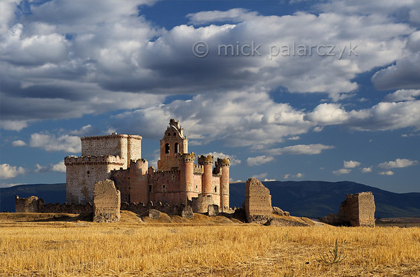 [SPAIN.CLEON 28568] 'Castle of Turégano.'  	The castle of Turégano has a complex history. It started out as a typical Moorish enclosure castle (an alcazaba) with an outer wall whose interval square towers can be seen in the foreground of this picture. In the 12th century the Romanesque church of San Miguel was built within the Moorish walls and this church was then incorporated in a late medieval castle whose white stoned keep is visible on the left. The church received a bell tower in the 18th century which rises above the red stoned inner curtain wall of the 15th century castle. Photo Mick Palarczyk.