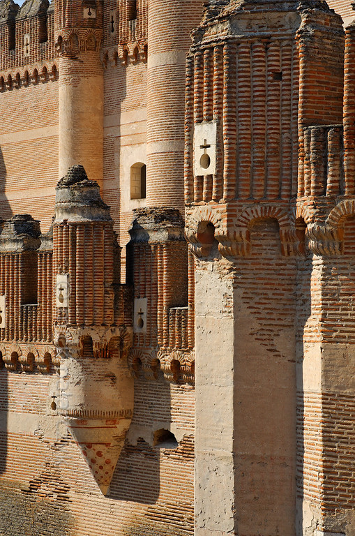 [SPAIN.CLEON 28599] 'Detail in east wall of Coca Castle.'   	The castle of Coca (Segovia province) was built in the second half of the 15th century by Alonso de Fonseca, the powerful archbishop of Seville and bishop of Ávila. The fortress is a beautiful example of the so-called Mudejar style: a mixture of Moorish and Christian style elements. It is brick-built because this was the principal material used by the Moorish master builders. Brick was the material with which it was possible to create the multitude of turret forms and details in the flat surfaces. Photo Mick Palarczyk.