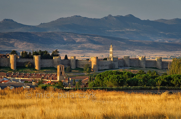 [SPAIN.CLEON 28609] 'Ávila seen from the north.'  	With the Sierra de Gredos in the background Ávila lies on a high plain, surrounded by two kilometers of medieval town walls and 88 towers. The walls were constructed around 1090, when the Castilian king Alfonso VI reconquered Muslim territory south of the Duero river. They replaced an earlier Roman fortification. The city was declared a World Heritage Site by Unesco in 1985. Photo Mick Palarczyk.