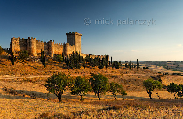 [SPAIN.CLEON 28627] 'Castle of Peñaranda de Duero.'  	The castle of Peñaranda (Burgos province), set on a hill just north of the Duero, was originally part of the 9th-11th century Moorish defense line against the Christians along this river. In the 10th century it was taken by the latter and was used as a centre of Christian repopulation on the northern margin of the Duero. The river (and the castles along it) formed the southern border of the Kingdom of Castile till the second half of the 11th century. Penaranda Castle was rebuilt in the 15th century. Photo Mick Palarczyk.