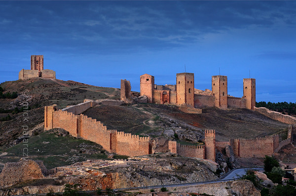 [SPAIN.CMANCHA 28536] 'Molina de Aragon.'  	The castle of Molina de Aragon (Guadalajara province) was founded by the Moors in the 10th century. It has the layout of a Moorish alcazaba: an extensive walled precinct with few buildings. Molina was conquered by the king of Aragon in 1129 and was rebuilt in the 12th and 13th century. The actual castle, with its four high towers, was built into a corner of the alcazaba precinct. Behind it, on the top of the hill, stands the so-called Tower of Aragon, which served as a kind of watchtower but is a castle in itself. Photo Mick Palarczyk.