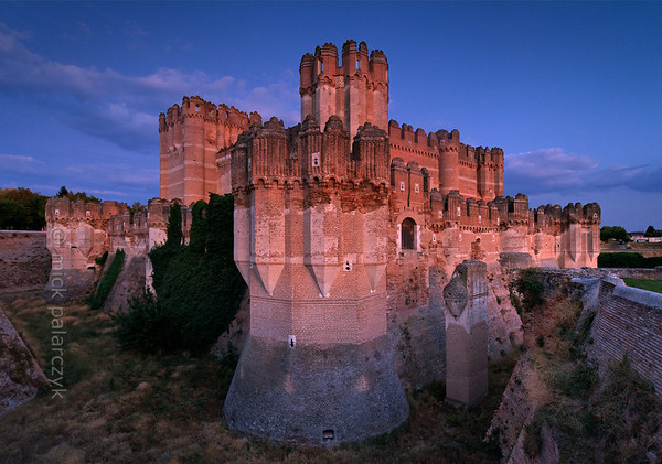 [SPAIN.CLEON 28592] 'Coca Castle seen from northwest.'  	The castle of Coca (Segovia province) was built in the second half of the 15th century by Alonso de Fonseca, the powerful archbishop of Seville and bishop of Ávila. The fortress is a beautiful example of the so-called Mudejar style: a mixture of Moorish and Christian style elements. It is brick-built because this was the principal material used by the Moorish master builders. Brick was the material with which it was possible to create the multitude of turret forms and details in the flat surfaces. Photo Mick Palarczyk.