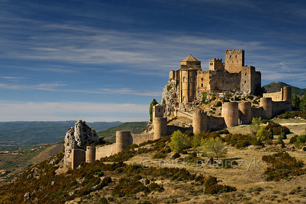 [SPAIN.ARAGON 28704] 'Castle of Loarre.'  	The castle of Loarre crowns a great outcrop of rock that juts out of the Pyrenean foothills north of the city of Huesca. The central core of the castle was built in 1020-1035 by king Sancho III of Navarra (and ruler of the emergent kingdom of Aragon) to protect his territory from the Moors in Huesca. In 1071 king Sancho Ramirez of Aragon extended the castle with a fortified (Augustinian) monastery and church, whose semicircular apse is visible on the left hand side of the building. The outer wall with circular defense towers was added in 1287. The castle was abandoned in the 15th century and has survived the centuries relatively untouched due to its inaccessibility. Photo Mick Palarczyk.