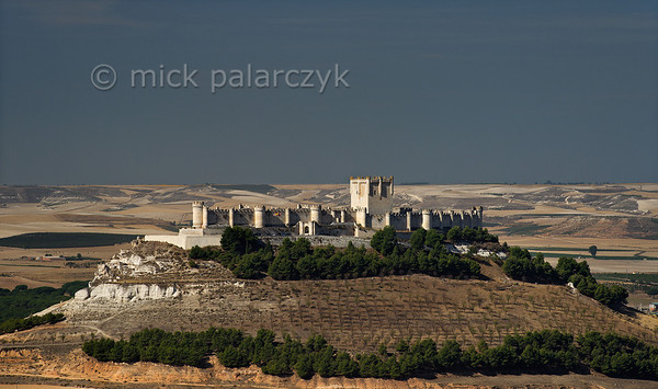 [SPAIN.CLEON 28640] 'Peñafiel Castle seen from the east.'  Peñafiel Castle (Valladolid province) sits atop a narrow ridge of limestone like an imitation of Noah's Ark stranded on the summit of Mount Ararat. The original castle on this site was part of the 9th-10th century Moorish defense line against the Christians along the Duero river. In 1013 it was taken by the Castilians and rebuilt in the 13th and 14th centuries. The central keep was finished in the 15th century. As Peñafiel is located in one of Spain's most famous vine growing regions, the castle nowadays is home to a Wine Museum. Photo Mick Palarczyk.