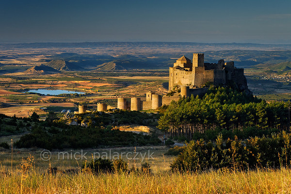 [SPAIN.ARAGON 28699] 'Castle of Loarre.'  	The castle of Loarre crowns a great outcrop of rock that juts out of the Pyrenean foothills north of the city of Huesca. The central core of the castle was built in 1020-1035 by king Sancho III of Navarra (and ruler of the emergent kingdom of Aragon) to protect his territory from the Moors in Huesca. In 1071 king Sancho Ramirez of Aragon extended the castle with a fortified (Augustinian) monastery and church. The outer wall with circular defense towers was added in 1287. The castle was abandoned in the 15th century and has survived the centuries relatively untouched due to its inaccessibility. Photo Mick Palarczyk.