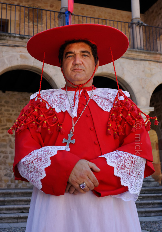 [SPAIN.CMANCHA 28543] 'Cardinal in Sigüenza.'  On the market square of Sigüenza, a small town in Guadalajara province, a street performer poses as a medieval cardinal wearing a red galero: a large, broad-brimmed hat with 15 tassels on each side. Photo Mick Palarczyk.