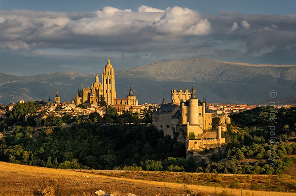 [SPAIN.CLEON 28572] 'Segovia seen from the west.'  The evening sun highlights the cathedral and Alcazar of Segovia against the backdrop of the Sierra de Guadarama. Photo Mick Palarczyk.