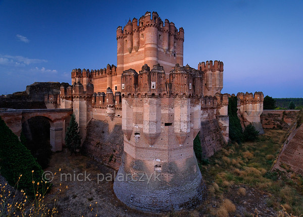 [SPAIN.CLEON 28595] 'Coca Castle seen from northeast.'  	The castle of Coca (Segovia province) was built in the second half of the 15th century by Alonso de Fonseca, the powerful archbishop of Seville and bishop of Ávila. The fortress is a beautiful example of the so-called Mudejar style: a mixture of Moorish and Christian style elements. It is brick-built because this was the principal material used by the Moorish master builders. Brick was the material with which it was possible to create the multitude of turret forms and details in the flat surfaces. Photo Mick Palarczyk.