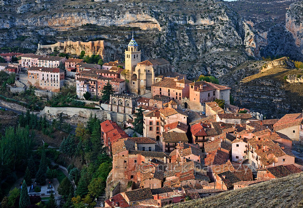 [SPAIN.ARAGON 28682] 'Albarracín and its castle.'  	Albarracín is a beautifully preserved medieval town in the canyon of the Guadalaviar river in the southwest of Teruel province. Its castle (in the upper left part of the picture) is a Moorish fort (alcazaba) of the 10th century, built during the caliphate of Córdoba. In the 11th century the town became the capital of a taifa, an independent Muslim state ruled by the Banu Razin dynasty, whose family name would lend the town its name (Sahla Banu Razin). From 1170 till 1285 it was the capital of the small independent Christian kingdom of the Azagra family. Its medieval cathedral was remodeled in the 16th and 18th centuries. Photo. Mick Palarczyk.