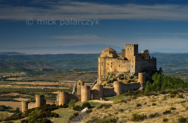 [SPAIN.ARAGON 28703] 'Castle of Loarre.'  	The castle of Loarre crowns a great outcrop of rock that juts out of the Pyrenean foothills north of the city of Huesca. The central core of the castle was built in 1020-1035 by king Sancho III of Navarra (and ruler of the emergent kingdom of Aragon) to protect his territory from the Moors in Huesca. In 1071 king Sancho Ramirez of Aragon extended the castle with a fortified (Augustinian) monastery and church, whose semicircular apse is visible on the left hand side of the building. The outer wall with circular defense towers was added in 1287. The castle was abandoned in the 15th century and has survived the centuries relatively untouched due to its inaccessibility. Photo Mick Palarczyk.