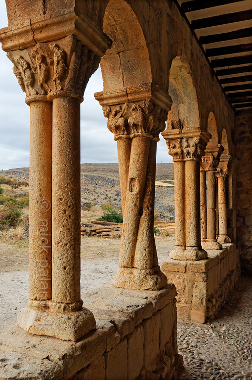 [SPAIN.CLEON 28657] 'Twisted columns in Caracena.'  	The 12th century church of San Pedro in the remote village of Caracena (Soria province) has a fine gallery with sculpted capitals. An odd pair of twisted columns flanks the entrance. From here it is a 500 meter uphill walk to Caracena Castle. Photo Mick Palarczyk.