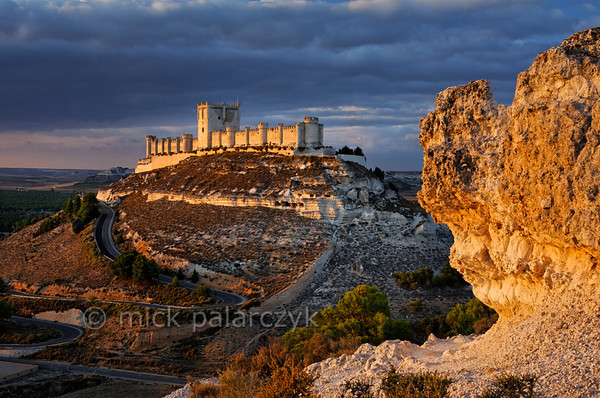 [SPAIN.CLEON 28637] 'Peñafiel Castle.'  Peñafiel Castle (Valladolid province) sits atop a narrow ridge of limestone like an imitation of Noah's Ark stranded on the summit of Mount Ararat. The original castle on this site was part of the 9th-10th century Moorish defense line against the Christians along the Duero river. In 1013 it was taken by the Castilians and rebuilt in the 13th and 14th centuries. The central keep was finished in the 15th century. As Peñafiel is located in one of Spain's most famous vine growing regions, the castle nowadays is home to a Wine Museum. Photo Mick Palarczyk.