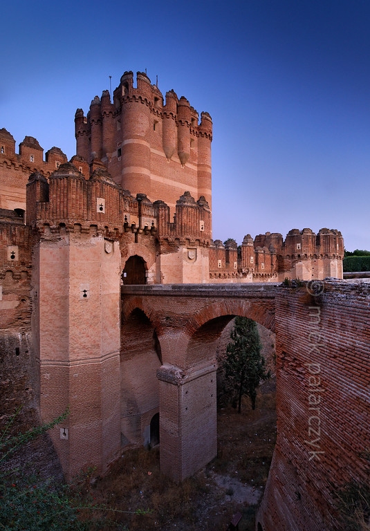[SPAIN.CLEON 28596] 'Moat of Coca Castle.'  	The castle of Coca (Segovia province) was built in the second half of the 15th century by Alonso de Fonseca, the powerful archbishop of Seville and bishop of Ávila. The fortress is a beautiful example of the so-called Mudejar style: a mixture of Moorish and Christian style elements. It is brick-built because this was the principal material used by the Moorish master builders. Brick was the material with which it was possible to create the multitude of turret forms and details in the flat surfaces. Photo Mick Palarczyk.