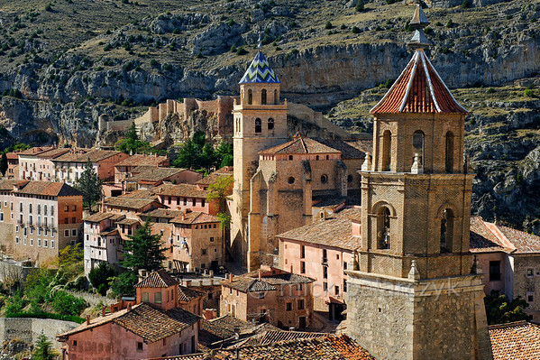 [SPAIN.ARAGON 28685] 'Albarracín and its castle.'  	Albarracín is a beautifully preserved medieval town in the canyon of the Guadalaviar river in the southwest of Teruel province. Its castle (visible in the background) is a Moorish fort (alcazaba) of the 10th century, built during the caliphate of Córdoba. In the 11th century the town became the capital of a taifa, an independent Muslim state ruled by the Banu Razin dynasty, whose family name would lend the town its name (Sahla Banu Razin). From 1170 till 1285 it was the capital of the small independent Christian kingdom of the Azagra family. Its medieval cathedral (with zigzag spire decoration) was remodeled in the 16th and 18th centuries. To the right we see the tower of the Santiago church. Photo. Mick Palarczyk.