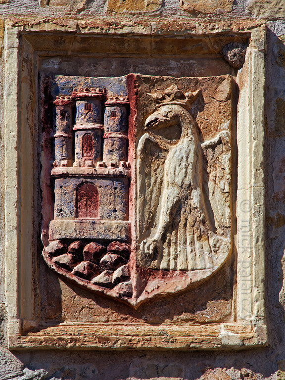 [SPAIN.CMANCHA 28547] 'Coats of arms of Sigüenza.'  	On the Plazuela de la Carcel in Sigüenza a facade shows the coats of arms of this small town in Guadalajara province. It is composed of the three towered castle of the Kingdom of Castile and a crowned eagle. Photo Mick Palarczyk.