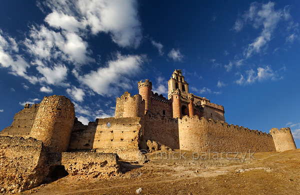 [SPAIN.CLEON 28571] 'Castle of Turégano.'  	The castle of Turégano has a complex history. It started out as a typical Moorish enclosure castle (an alcazaba) with an outer wall whose remnants can be seen on the left. In the 12th century the Romanesque church of San Miguel was built within the Moorish walls and this church was then incorporated in a late medieval castle which is visible on the right. The church received a bell tower in the 18th century which rises above the red stoned inner curtain wall of the 15th century castle. Photo Mick Palarczyk.