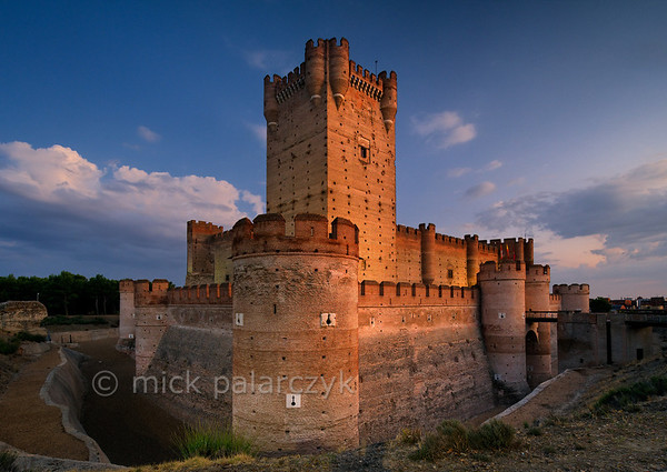 [SPAIN.CLEON 28648] 'Castillo de La Mota in Medina del Campo.'  	The impressive Castillo de La Mota is located on a hill just east of Medina del Campo (Valladolid province) which was one of the most important market towns of Spain at the end of the middle ages. The oldest part of the current castle dates from around 1200 when the Castilian king Alfonso VIII built his modest castle on the remains of a Moorish villa. It was enlarged during 13th - 15th century and Moorish (Mudejar) masons were employed for the brickwork, just as in the castle of Coca, further east. Photo Mick Palarczyk.