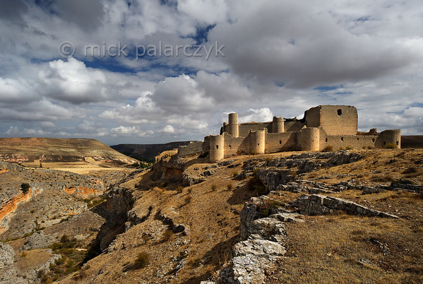 [SPAIN.CLEON 28653] 'Caracena Castle seen from the south.'  In the remote mountains of southern Soria province the ruined castle of Caracena balances on the edge of a gorge that empties into the Rio Caracena. The castle originally dates from the 12th century but was completely rebuilt in 15th. Photo Mick Palarczyk.