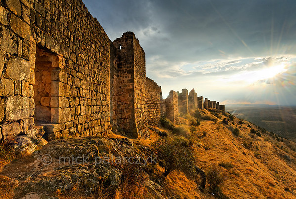 [SPAIN.CLEON 28664] 'North wall of Gormaz Castle.'  	The castle of Gormaz (Soria province) was built in the 9th century and reinforced in 965 by Caliph Al-Hakam II of Córdoba to defend Moorish territory. Built on a steep narrow ridge, just north of the Duero, it was the most important fortress along this river that formed the boundary between Moslem and Christian lands in the 9th - 11th century. It was conquered and reconquered several times by both sides. In 1087 King Alfonso VI of Castile gave it to El Cid. The fortress, which is one of the biggest in Europe, has the layout of a typical Moorish alcazaba: an extensive walled precinct with a perimeter of 1 km that could house a large garrison. Photo Mick Palarczyk.