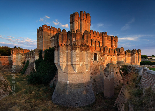 [SPAIN.CLEON 28591] 'Coca Castle seen from northwest.'  	The castle of Coca (Segovia province) was built in the second half of the 15th century by Alonso de Fonseca, the powerful archbishop of Seville and bishop of Ávila. The fortress is a beautiful example of the so-called Mudejar style: a mixture of Moorish and Christian style elements. It is brick-built because this was the principal material used by the Moorish master builders. Brick was the material with which it was possible to create the multitude of turret forms and details in the flat surfaces. Photo Mick Palarczyk.