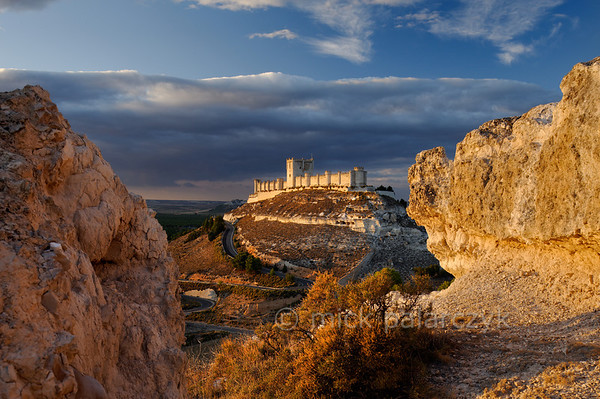 [SPAIN.CLEON 28636] 'Peñafiel Castle.'  Peñafiel Castle (Valladolid province) sits atop a narrow ridge of limestone like an imitation of Noah's Ark stranded on the summit of Mount Ararat. The original castle on this site was part of the 9th-10th century Moorish defense line against the Christians along the Duero river. In 1013 it was taken by the Castilians and rebuilt in the 13th and 14th centuries. The central keep was finished in the 15th century. As Peñafiel is located in one of Spain's most famous vine growing regions, the castle nowadays is home to a Wine Museum. Photo Mick Palarczyk.
