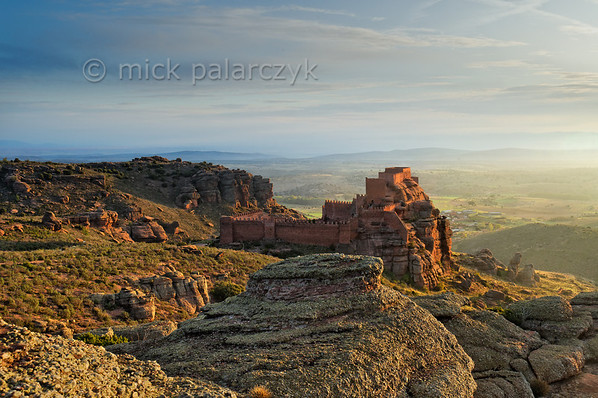 [SPAIN.ARAGON 28692] 'Castle of Peracense.'  	The castle of Peracense sits atop a remote crag of red sandstone in the Sierra de Almohaja (Teruel province). It is first mentioned in 1284 when King Pedro III of Aragon used it as a base for capturing the independent Christian kingdom of Azagra whose capital Albarracín lies 25 km to the south. In the 14th century it played a role in the wars between Castile and Aragon because its location commands the gorge through which invading armies could pass between the two kingdoms. Photo Mick Palarczyk.