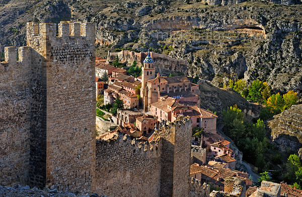 [SPAIN.ARAGON 28688] 'Albarracín and its town wall.'  	Albarracín is a beautifully preserved medieval town in the canyon of the Guadalaviar river in the southwest of Teruel province. Its town wall (visible in the foreground) is partly of Moorish 10th -11th century origin and partly of 13th century Christian origin. In the 11th century the town was the capital of a taifa, an independent Muslim state ruled by the Banu Razin dynasty, whose family name would lend the town its name (Sahla Banu Razin). From 1170 till 1285 it was the capital of the small independent Christian kingdom of the Azagra family. Photo Mick Palarczyk.