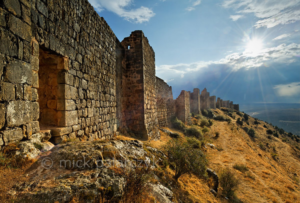 [SPAIN.CLEON 28662] 'North wall of Gormaz Castle.'  	The castle of Gormaz (Soria province) was built in the 9th century and reinforced in 965 by Caliph Al-Hakam II of Córdoba to defend Moorish territory. Built on a steep narrow ridge, just north of the Duero, it was the most important fortress along this river that formed the boundary between Moslem and Christian lands in the 9th - 11th century. It was conquered and reconquered several times by both sides. In 1087 King Alfonso VI of Castile gave it to El Cid. The fortress, which is one of the biggest in Europe, has the layout of a typical Moorish alcazaba: an extensive walled precinct with a perimeter of 1 km that could house a large garrison. Photo Mick Palarczyk.