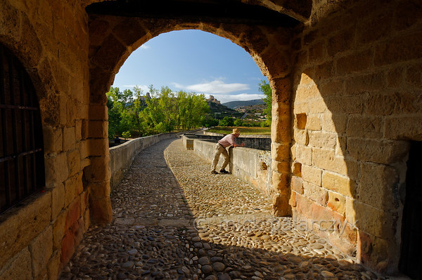 [SPAIN.CLEON 28625] 'Medieval bridge and castle at Frías.'  The medieval bridge at Frías (Burgos province) crosses the Ebro with nine arches over a distance of 143 meters. It was built on earlier Roman foundations. The picture is taken from under the central defense tower which was added in the 14th century to provide a convenient location for  taking toll. We are looking in the direction of the town of Frias, whose castle is visible on the hill in the distance. Photo Mick Palarczyk.