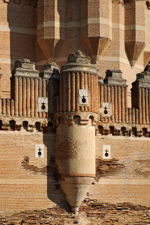 [SPAIN.CLEON 28597] 'Detail in south wall of Coca Castle.'  	The castle of Coca (Segovia province) was built in the second half of the 15th century by Alonso de Fonseca, the powerful archbishop of Seville and bishop of Ávila. The fortress is a beautiful example of the so-called Mudejar style: a mixture of Moorish and Christian style elements. It is brick-built because this was the principal material used by the Moorish master builders. Brick was the material with which it was possible to create the multitude of turret forms and details in the flat surfaces. Photo Mick Palarczyk.