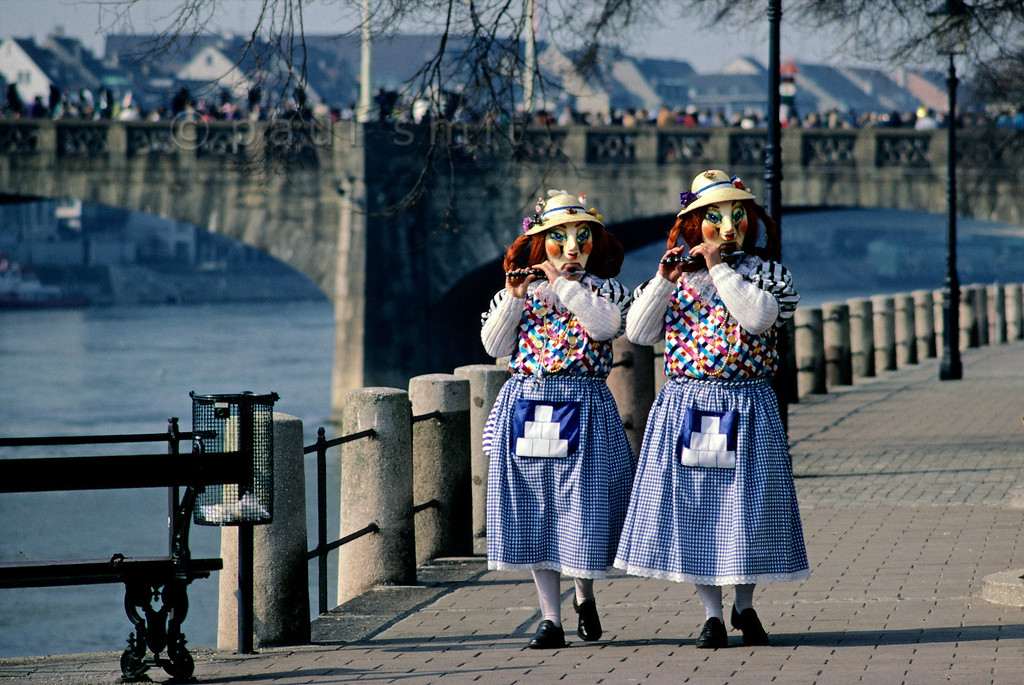 [SWITZER.JURA 6317] 'Old spinsters along the Rhine.'  During the <i>Basler Fasnacht</i> (carnival in Basel) two <i>Alti Dantes</i> (old spinsters) pipe along the Rhine. Mind you, in daily life they are a couple. The man is at right. Photo Paul Smit.
