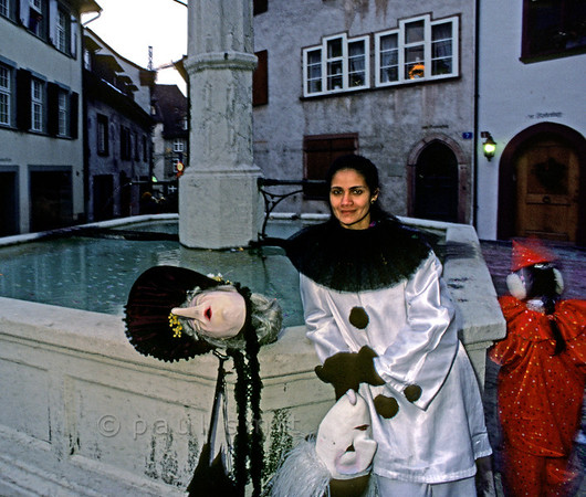 "[SWITZER.JURA 6338] ""Face behind the mask.'  During the Basler Fasnacht (carnival of Basel) it can be a pleasant surprise to see who is behind a mask. Especially if that mask, called a Larve in Basel, has the face of an Alti Dante, an old spinster. Photo Paul Smit."