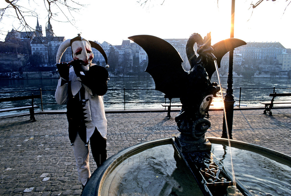 [SWITZER.JURA 6329] 'Fool at the Rhine.'  Along the Rhine (Rhein) the <i>Basler Fasnacht</i> (carnival of Basel) lives through some its most beautiful moments when the sun sets behind the Münster church. I followed this fool for half an hour when he walked through the old streets, along the river and over the bridges. He didn't stop piping. As a real Basler he knew what Fasnacht was about: scaring the winter away! Photo Paul Smit.
