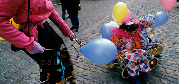[SWITZER.JURA 6353] 'Speed.'  Tuesday is children's carnival during the Basler Fasnacht, the carnival of Basel. Then the children rule and the parents obey. These children are enjoying a wild ride while their father (!) is running across the square. Photo Paul Smit.