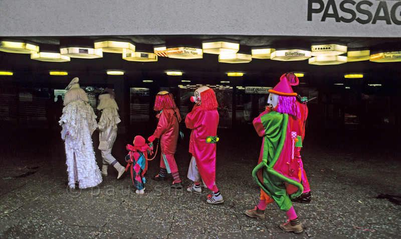 [SWITZER.JURA 6326]<br /> 'Carnival in surreal surroundings.'<br /> <br /> A family of clowns and other strange folk entering the Theater Passage during the carnival in Basel. Photo Paul Smit.