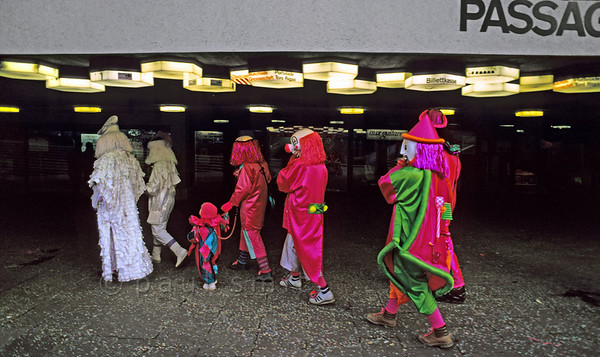 [SWITZER.JURA 6326] 'Carnival in surreal surroundings.'  A family of clowns and other strange folk entering the Theater Passage during the carnival in Basel. Photo Paul Smit.
