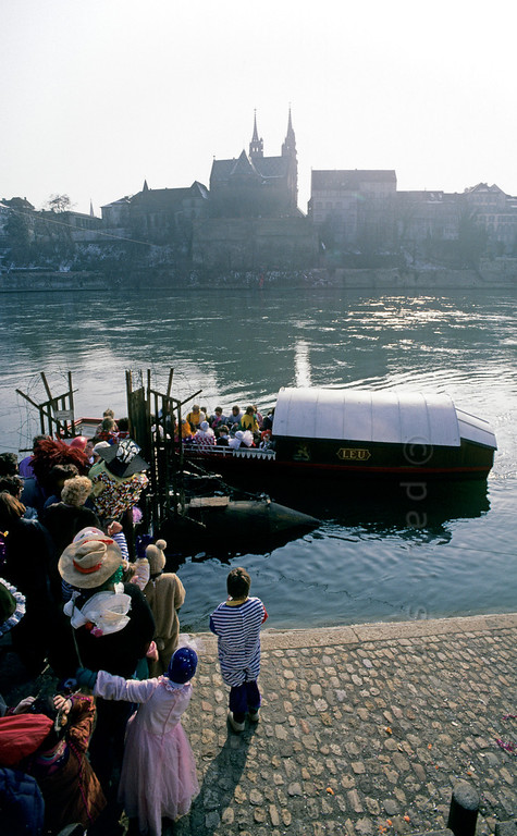 [SWITZER.JURA 6351] 'Carnival queue.'  Queing for the ferry over the Rhine (Rhein) during the Basler Fasnacht, the carnival of Basel. There are three ferries in town, and none has a motor. They use a cable and the force of the streaming water. Photo Paul Smit.