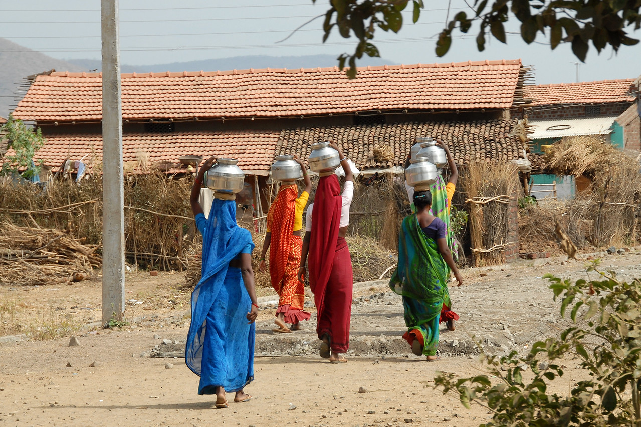 India: Group of women returning to their village after filling water from the the community well  which is fitted with a hand pump. The women typically carry the water in vessels balanced on their heads. This image was taken in a village near Nagpur, Maharashtra, India Jan 2007.