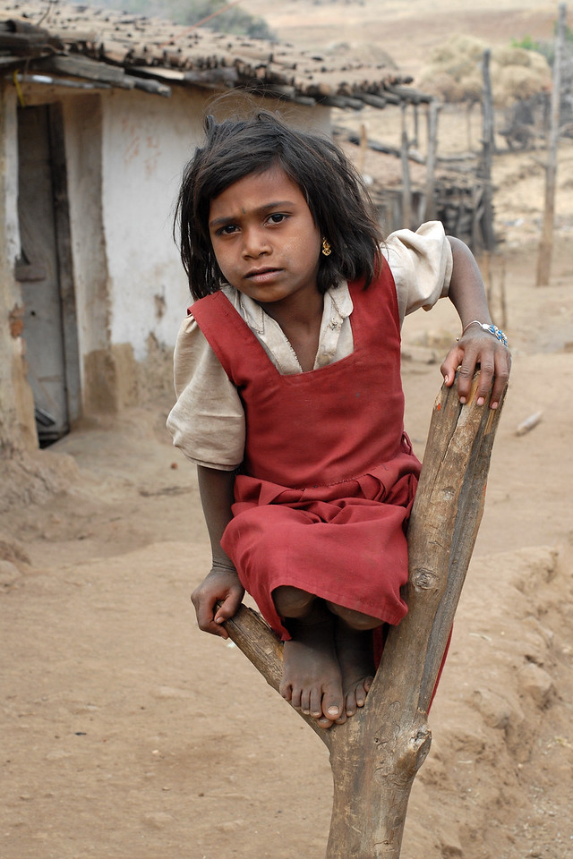 """India: """"Delicate Balance in Life"""": This girl in her school uniform was sitting on the wooden branch outside her house in a village near Nagpur, Maharashtra. When visiting the villages (in India) its hard not to get moved by the level of poverty in the country side and to experience the feeling of helplessness that they feel. Jan 2007."""