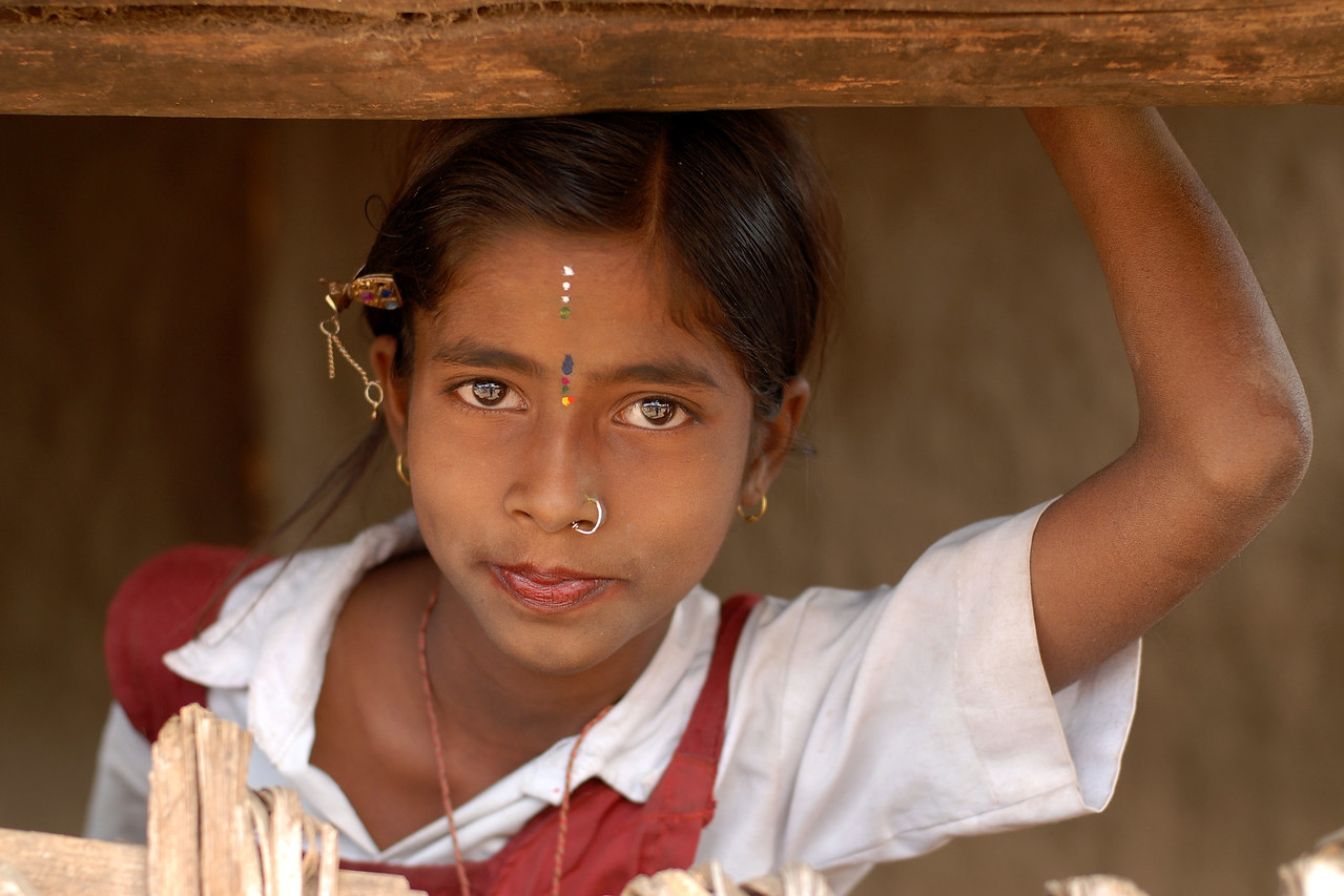 "India: ""Bejewelled"": This girl in her school uniform, came to the entrance of her home and peeped out when I got this image. In a few fleeting moments she was gone as she hopped and skipped away. Jan 2007."