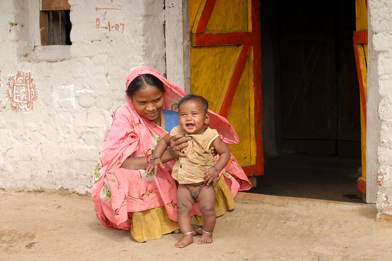 India: Mother with her smiling son sitting at the entrance to their home in a village near Nagpur, Maharashtra. Jan 2007.