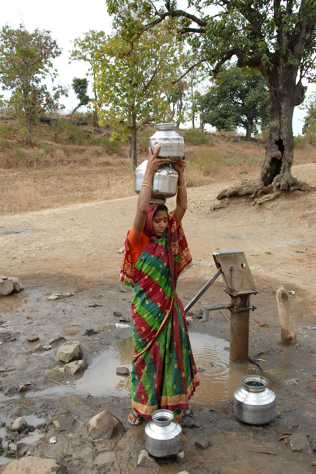 India: This young lady is preparing for the multiple pots that will go on her head which will carry the water from the local village hand pump in a village near Nagpur, Maharashtra. Seen in the fore ground are the vessles which she will be carrying. Jan 2007.