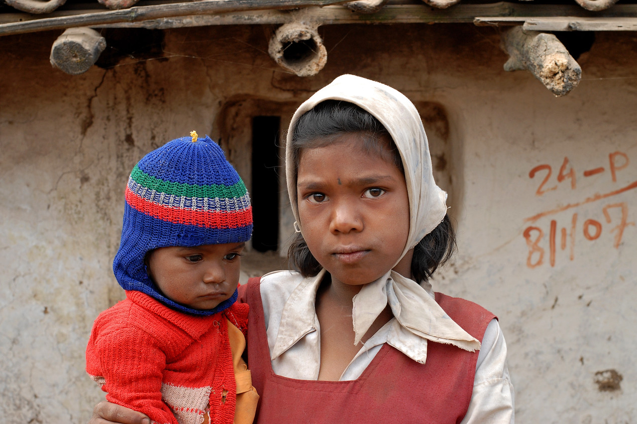 India: Sister carrying her brother in a village near Nagpur, Maharashtra. Jan 2007.