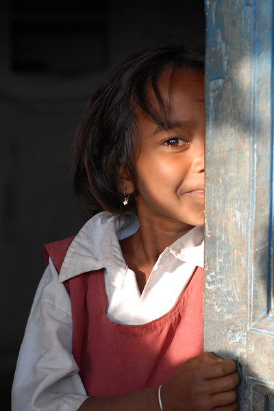 Shy little girl in her school uniform peeping from behind the door to her house.