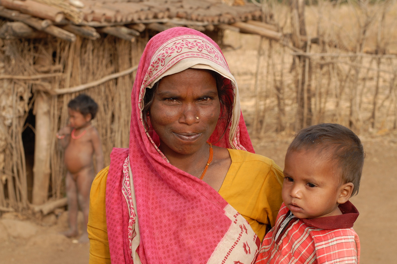India: A lady holding her son while her daughter plays behind her and in front of their home in rural Nagpur. 07; Mar; 07.