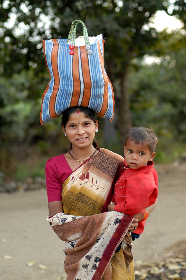 India: Lady with her child and a large bag on her head was walking back towards her village located near Nagpur, Maharashtra. Its amazing how well they balance these bags and the loads they can carry over long distances. Jan 2007