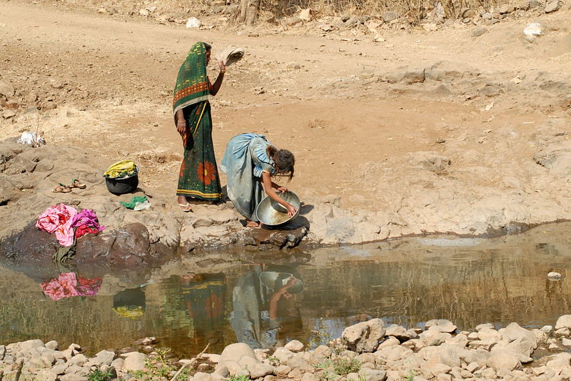 India: Water is scarce, and any water source serves as an area to collect water to drink, to wash cloths and vessels and do the laundry. This image is taken in a village near Nagpur, Maharashtra, India Jan 2007.