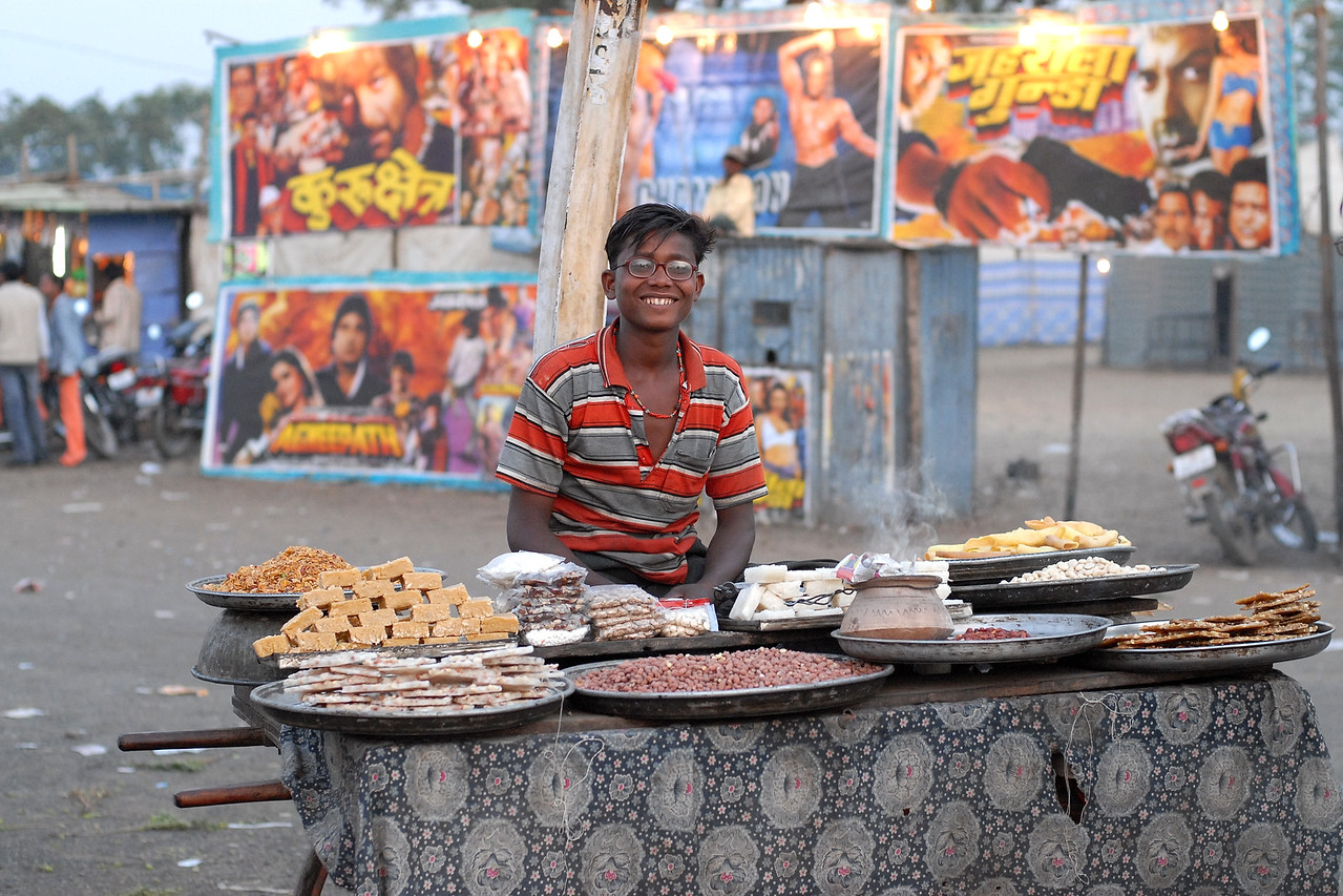 "A vendor sells sweets, peanuts and chickpeas (channa) heated in the small earthen pot at a village fair known as ""Haat"". In the background is a ""talkis"", a cheap form of cinema. Nagpur, Maharashtra, India. January 28, 2007."