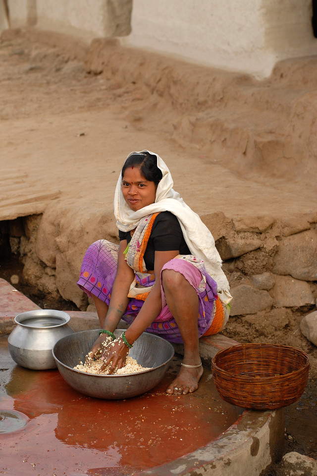India: This young lady is soaking and washing the lentils (Daal) in a vessel outside her home in a village near Nagpur, Maharashtra. Jan 2007.